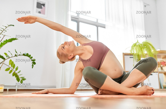 happy pregnant woman doing yoga at home