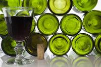 Rotweinglas und Korken vor leeren Weinflaschen