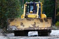 Crawler bulldozer rides on a dirt road
