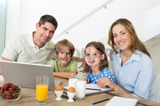 Portrait of family using laptop while having breakfast