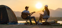 Asian couple with dog playing guitar and drinking beer beside their tent campsite panorama
