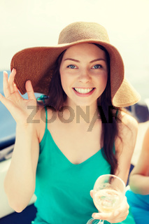 smiling girl in hat with champagne glass