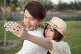 Young couple with mobile phone self-timer