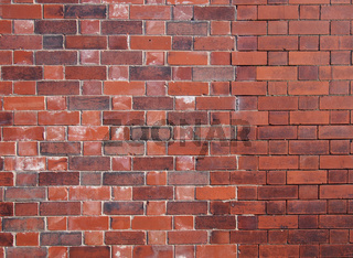 an old repaired patched exterior wall made of red bricks