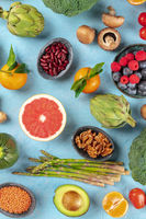 Vegan food, healthy diet top flat lay shot. Fruits, vegetables, legumes, mushrooms, nuts, shot from the top on a blue background