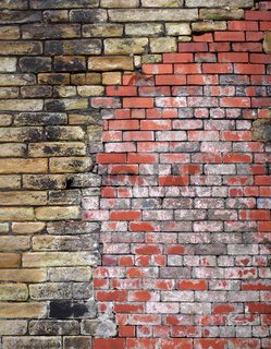 an old repaired exterior wall made of stone patched with bricks