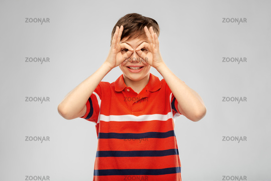 happy smiling boy looking through finger glasses