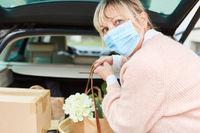Frau mit Mundschutz und Einkäufen vor Kofferraum