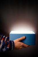 blaue Geschenkbox mit Lichtschein vor schwarzem Hintergrund