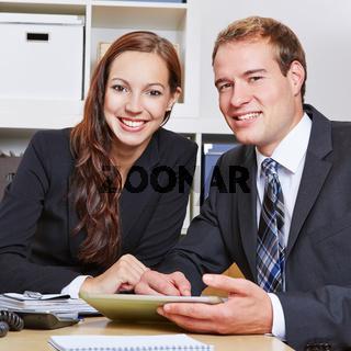 Zwei lächelnde Geschäftsleute im Büro