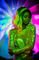 Sexy young woman in neon glow. Stylish girl in sparkling dress posing on bright colourful or multicoloured background in disco style. Vogue concept