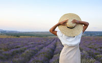 Beautiful woman in straw hat in violet lavender field