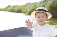 Happy kid sitting wearing hat in the boat