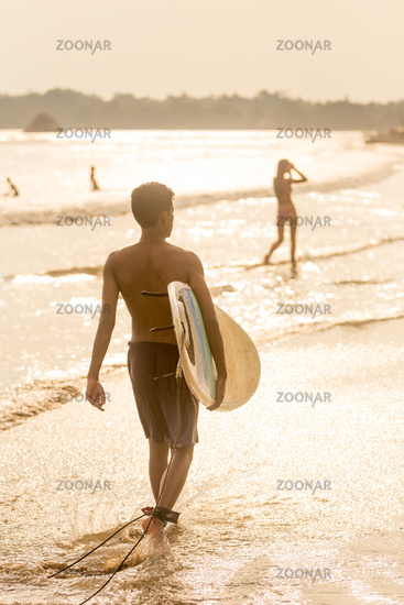 Man walking at tropical beach of Midigama, Sri Lankha at sunsen with surf board in his hands.