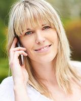 Frau telefoniert mit Smartphone in Natur