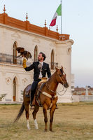A Very Handsome Mexican Charro Poses In Front Of A Hacienda In The Mexican Countryside While Holding His Pet Falcon