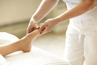 Crop masseuse making feet massage to client