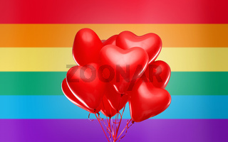 red heart shaped helium balloons over rainbow flag