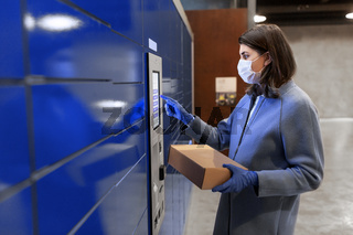 woman in mask with box at parcel machine