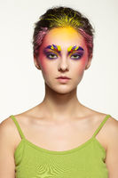 Female portrait with unusual face art make-up. Paint on brows, hair and around eyes.
