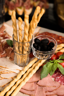 Prosciutto and meat assorted. Breadsticks with meat slicing. Close up shot. Holiday or event treats. Catering food concept