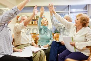 Senioren machen mit den Händen eine Übung für Zusammenhalt in der Gruppentherapie