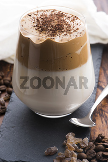 Dalgona coffee in glass cup. Korean trendy drink from instant coffee, milk and brown sugar