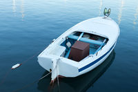Vintage old white wooden row boat on blue sea water