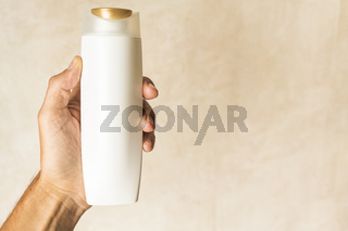 left hand holding modern container with golden cap, blurred warm colored background