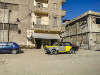 A black and yellow dilapidated Lada taxi driving through the beaten road in Alexandria