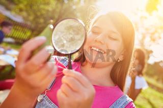 Kind betrachtet Birne mit Lupe bei Umweltschutzprojekt