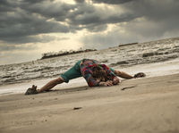 Unrecognizable man doing yoga on stormy seashore
