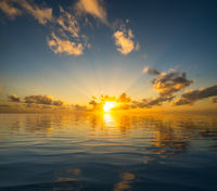 Beautiful sunset reflected in a calm peaceful ocean as concept for peace