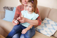 Grandmother cleaning hands of little daughter