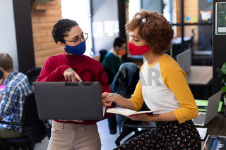 Two mixed race women wearing face masks using laptop and discussing in office