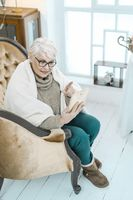 Old Grey-haired Woman Having A Rest At Home With A Tablet in Her Hand.