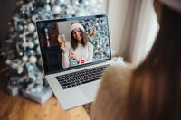 Female wearing santa hat while speaking with online friend on laptop