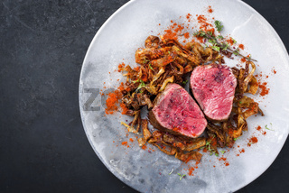 Barbecue dry aged beef fillet medaillon steak natural with fried onion rings and carrots as top view on a modern design plate with copy space left