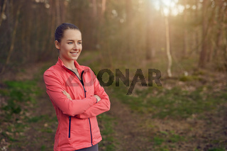 Happy confident young woman in woodland