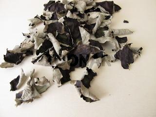 Fermentierte und getrocknete Brombeerblätter für koffeinfreien Schwarztee auf einem Holzbrett