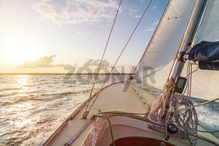 Sailing boat sailing fast into the beautiful sunset during choppy sea