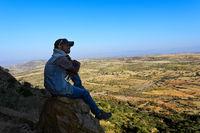 Junger einheimische Mann sitzt auf einem Stein und blickt über die Landschaft im Hochland von Abessinien