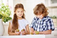 Zwei Kinder schneiden Kiwi in Küche