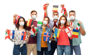 people in respirators with international flags