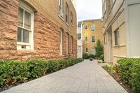Pathway amid residential buildings leading to a fire pit in the distance