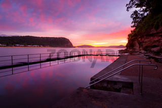 Red and pink dawn skies and reflections in the rock pool