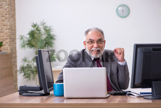 Old male boss sitting at desktop in the office