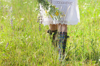 Anonymous woman with flowers walking in field