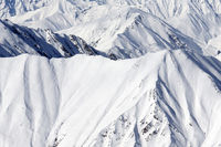 High mountains with sunlit snowy slope at winter day