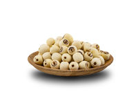 Pile of Dried Lotus Seeds in a wooden plate on white background.